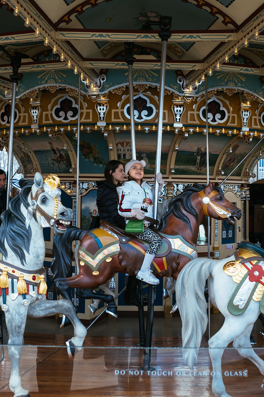 child riding a merry go round