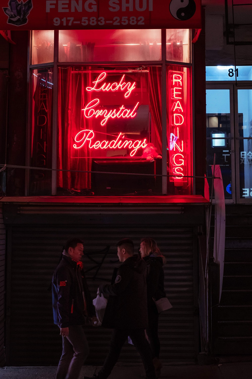people talking under a neon sign
