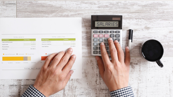 Understanding the Nuances of Executive Compensation Packaging Blog man using calculator on desk