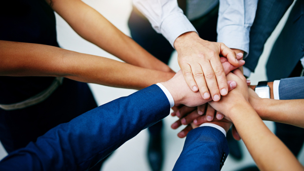 The Value of Team Building in the Workplace employees hands stacked on one another inside a circle
