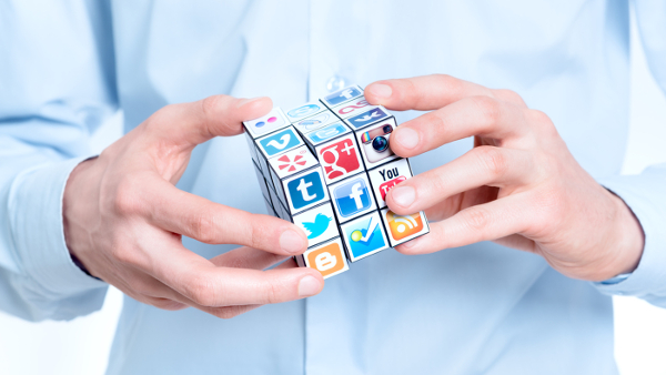 Social Media Do's and Don'ts for Professionals and Job Seekers; Businessman rotating a rubik's cube with logotypes of well-known social media brands