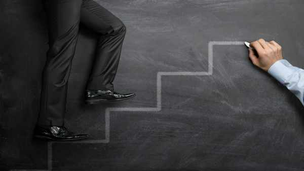 How to Advance from Entry Level to Middle Management | man climbing ladder on chalkboard