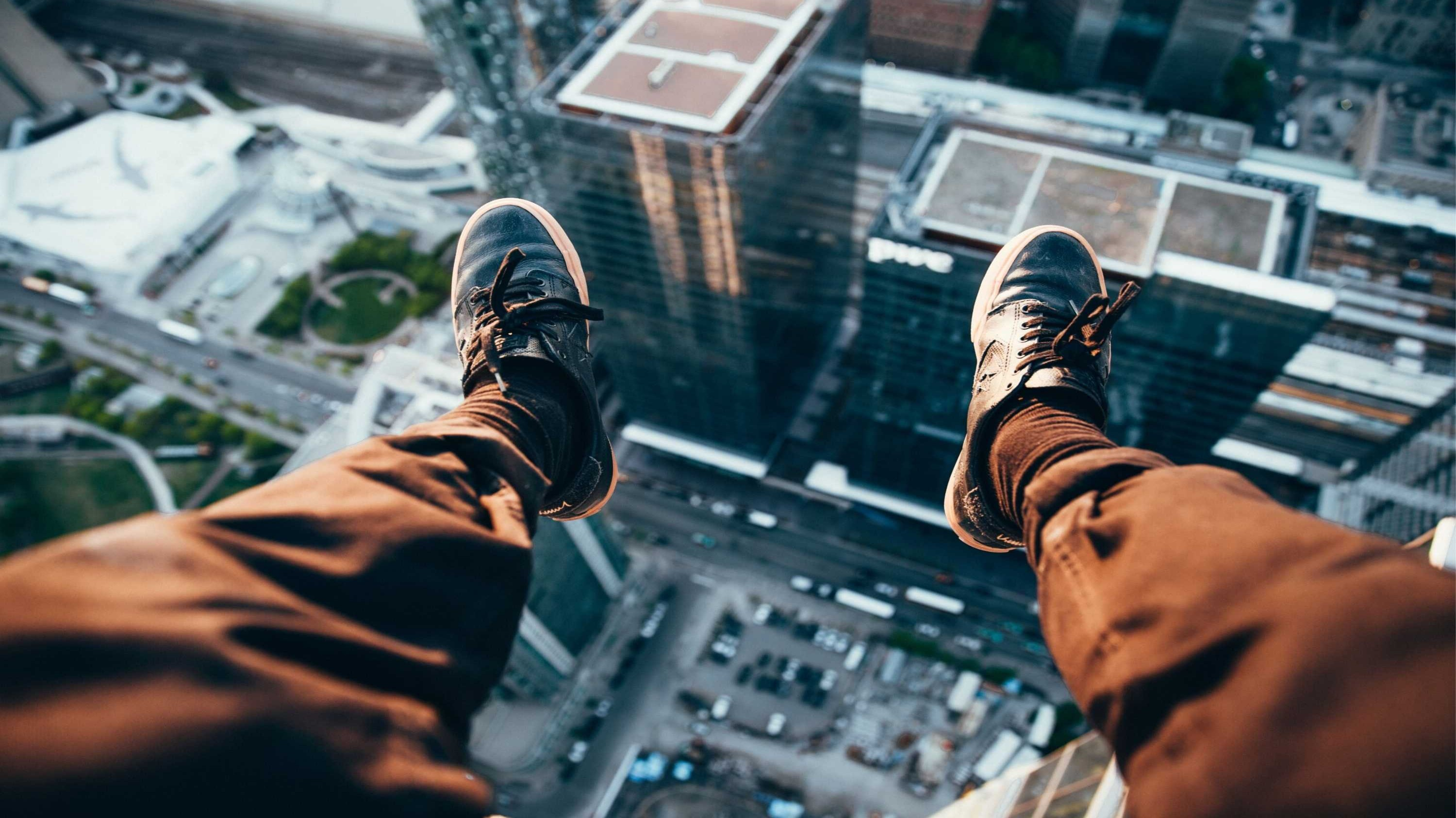Our Best Career Advice In (2) Words image of man dangling his feet over an edge