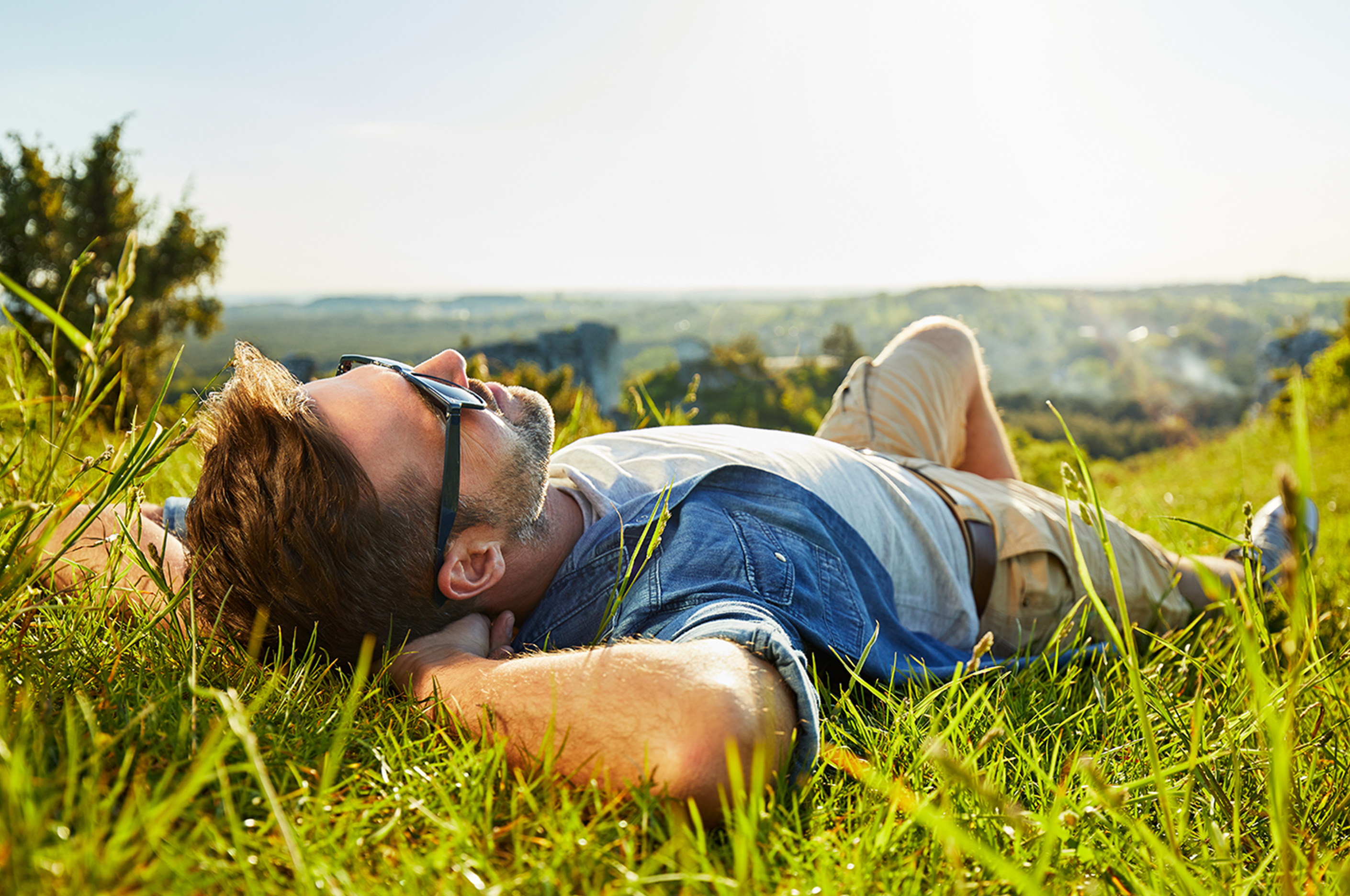 Man laying on grass, enjoying some sunshine