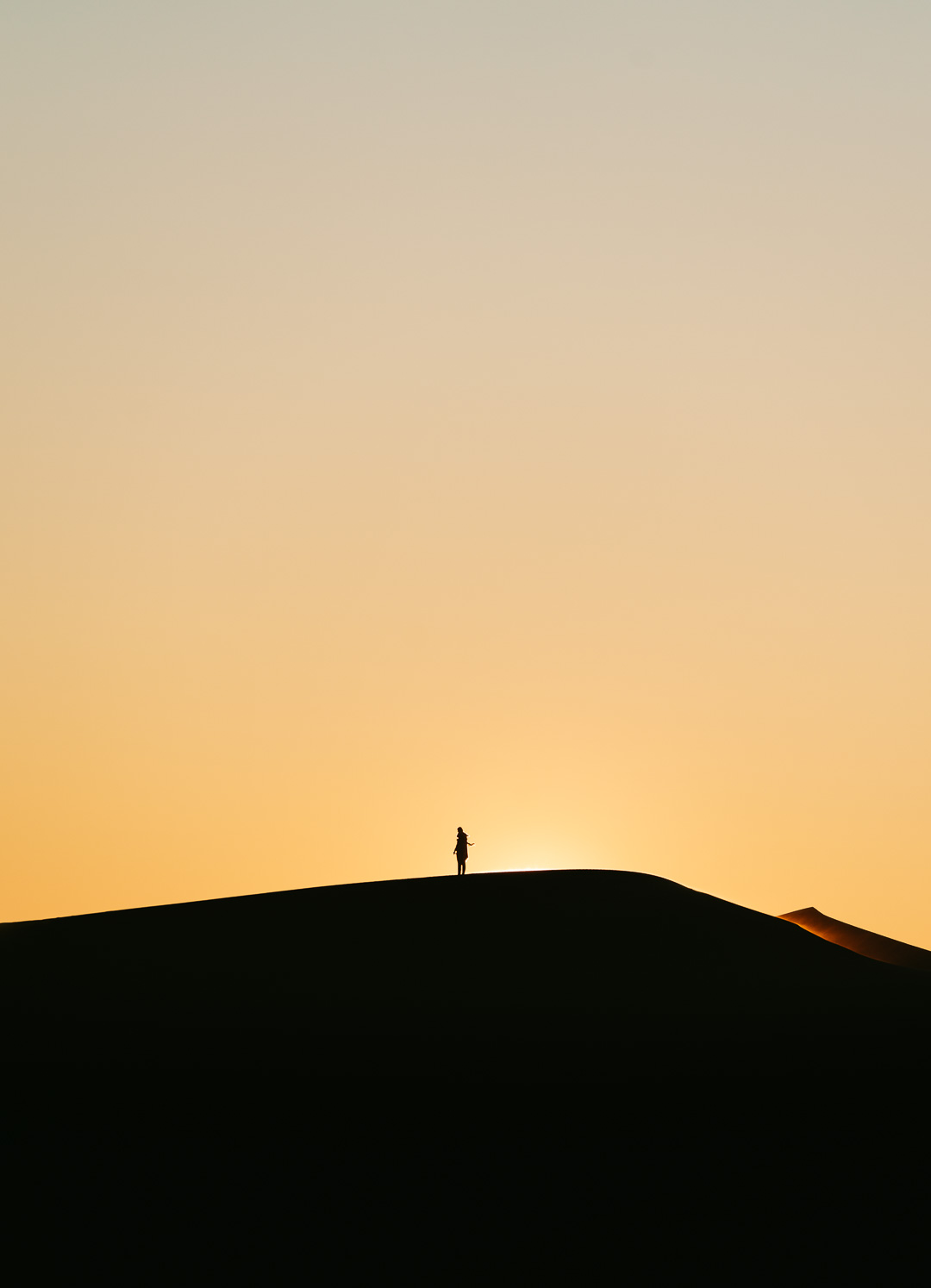 Silhouette of person at sunrise in the Sahara desert