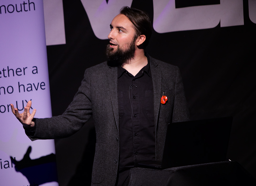 A bearded man wearing a blazer, either public speaking or summoning a demon.