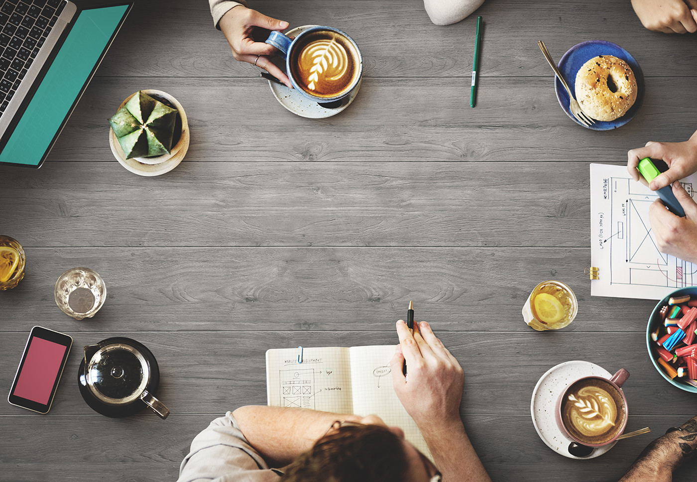 hands planning at a table with notebooks coffee and bagel