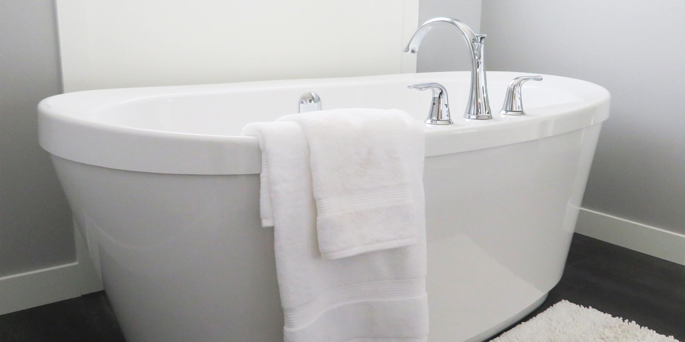 Fluffy white towel hanging on a bath tub