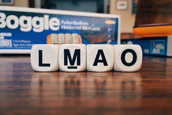 LMAO spelt out in boggle game letters on wooden table