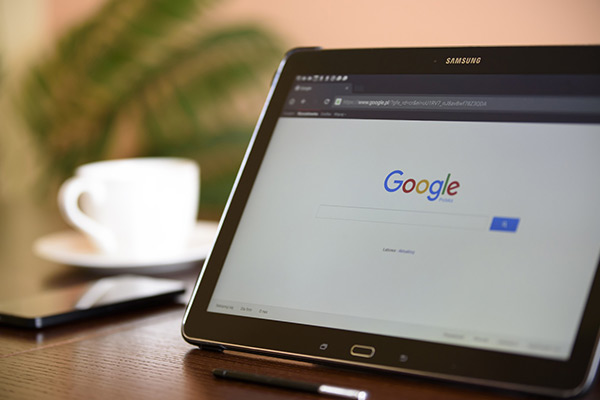 Google search window on a laptop with mobile and coffee cup in background