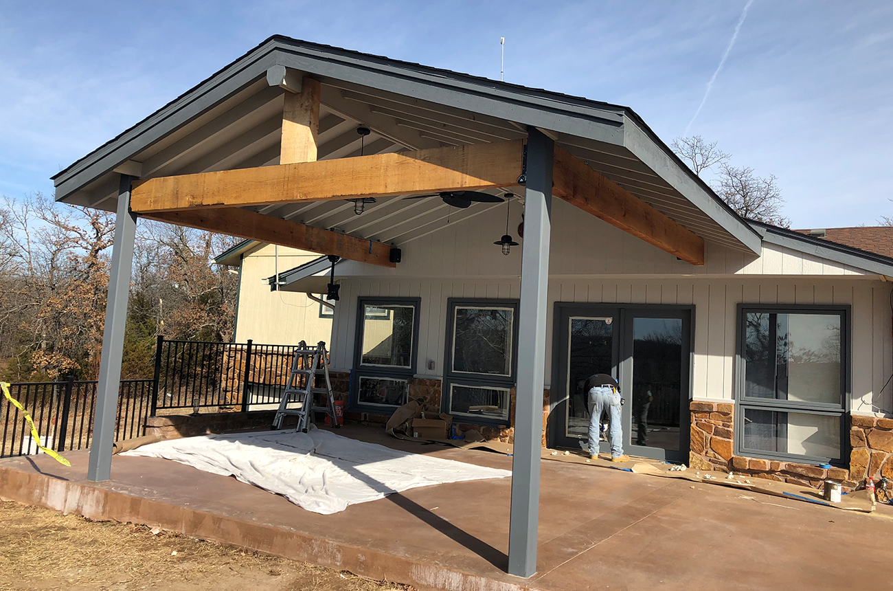 This custom carport features a new stamped and stained concrete driveway, lights, ceiling fan, flat screen TV mount and four speakers.