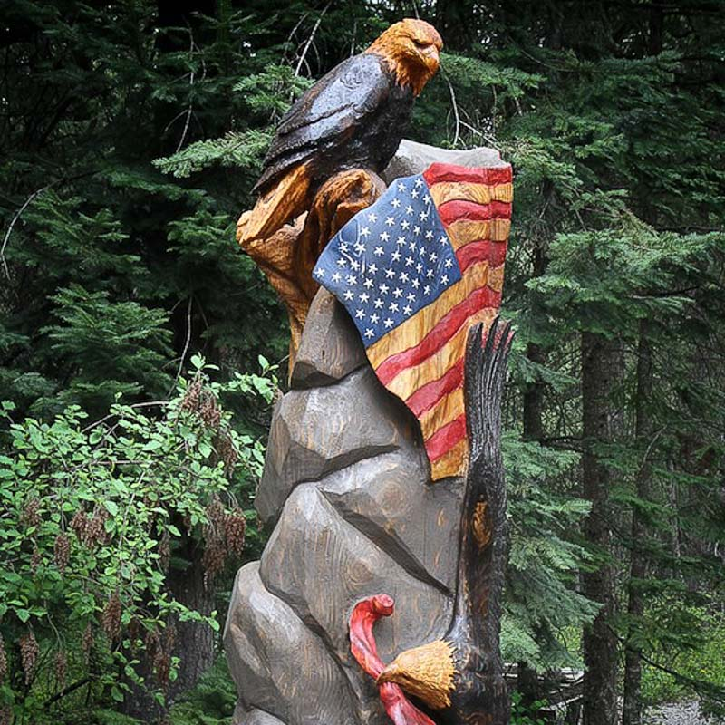 wood carved tree with an american flag and bald eagle