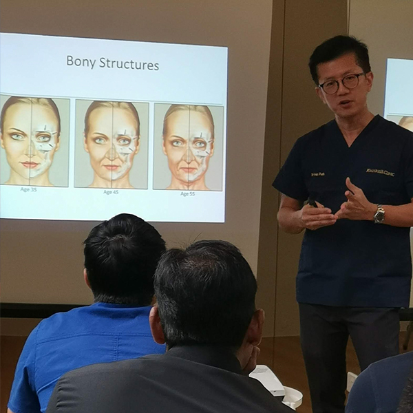 Dr. Ivan Puah conducting a theory session for fellow doctors on facial anatomy.