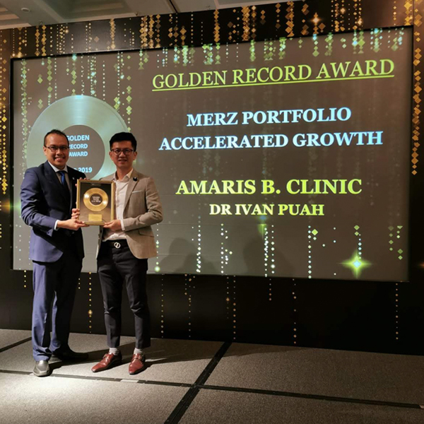 "Dr. Ivan Puah receiving a ""Golden Record Award"" on Accelerated Growth from Merz Aesthetics Singapore"