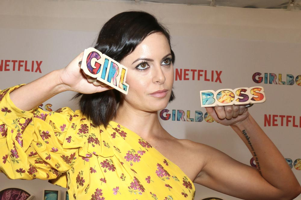 Sevědomá Sophia Amoruso pózující s barevným nápisem GIRL BOSS.