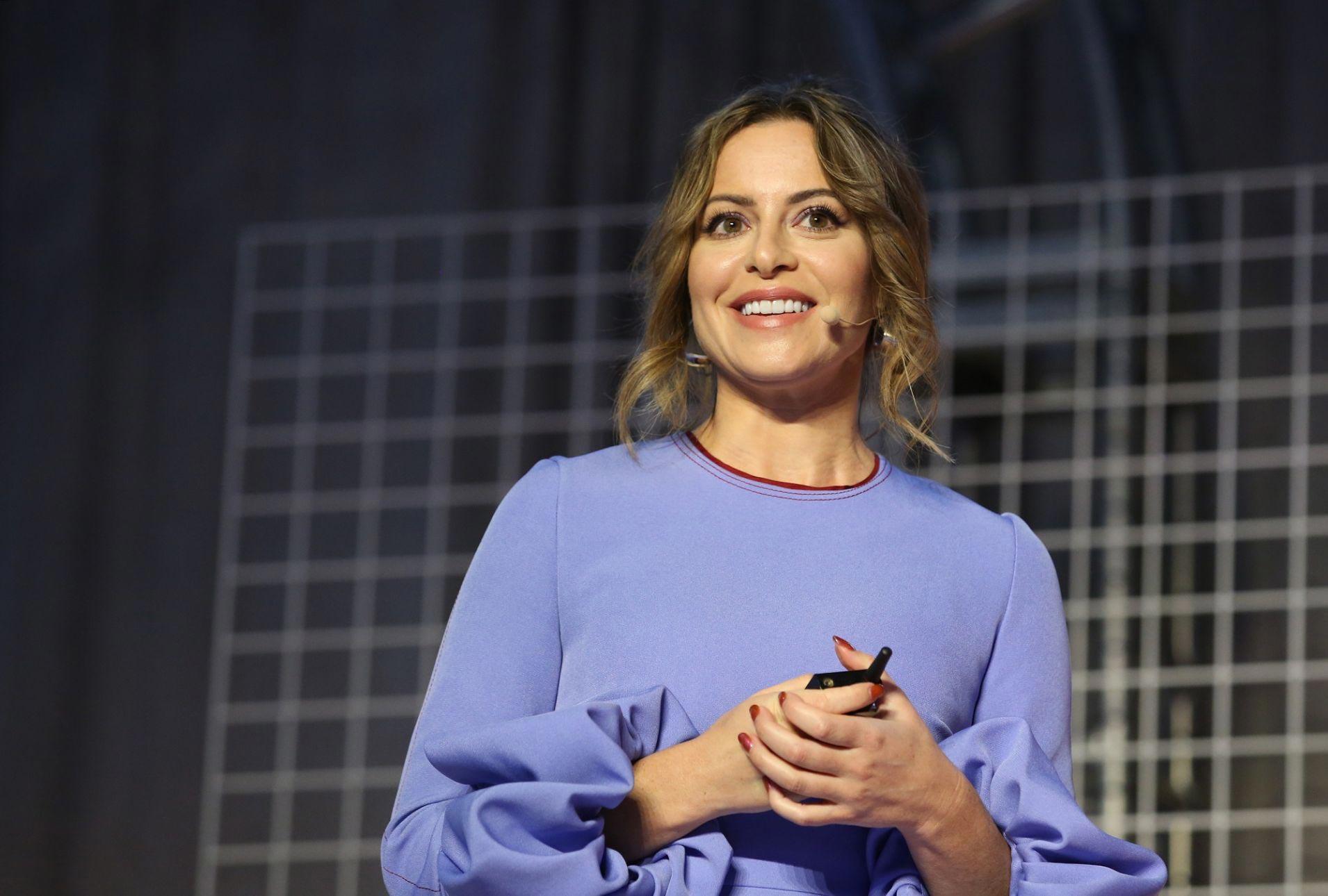 Sophia Amoruso v modrých šatech přednášející na konferenci svému publiku.