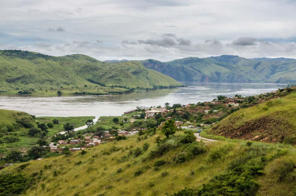 Krásná zelená příroda v Kongu, ve které se nachází vesnice i široká řeka.