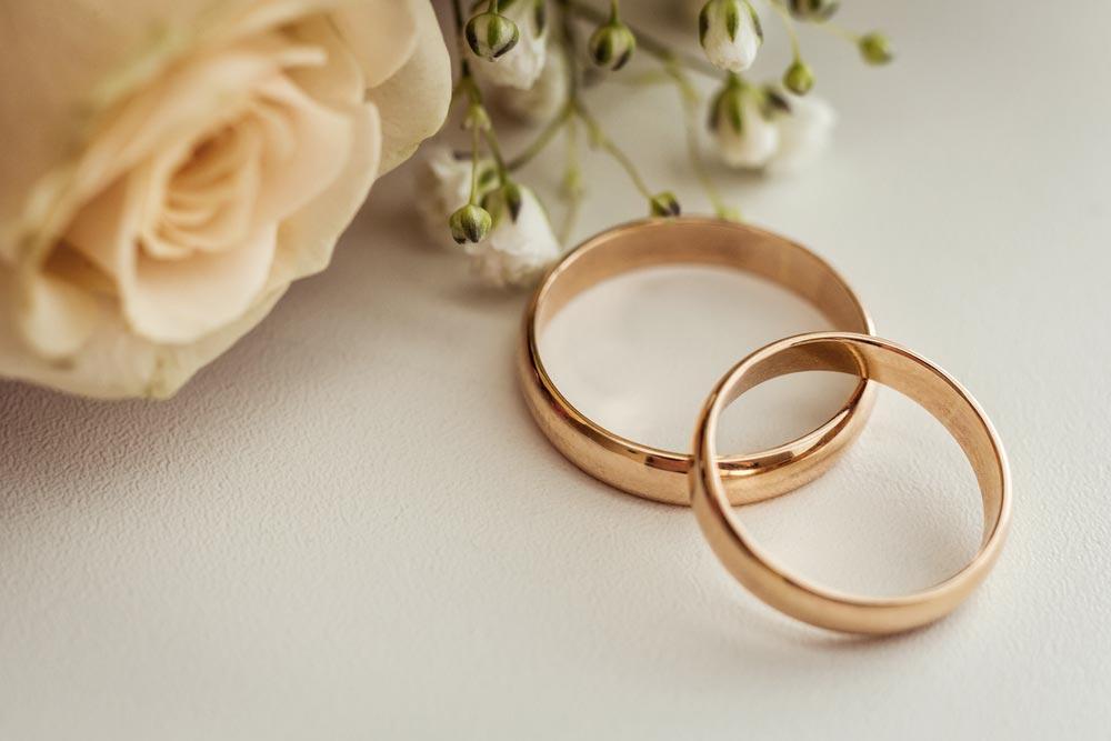 2 zlaté prstýnky ležící na bílém a čerstvě prostřeném svatebním stole.