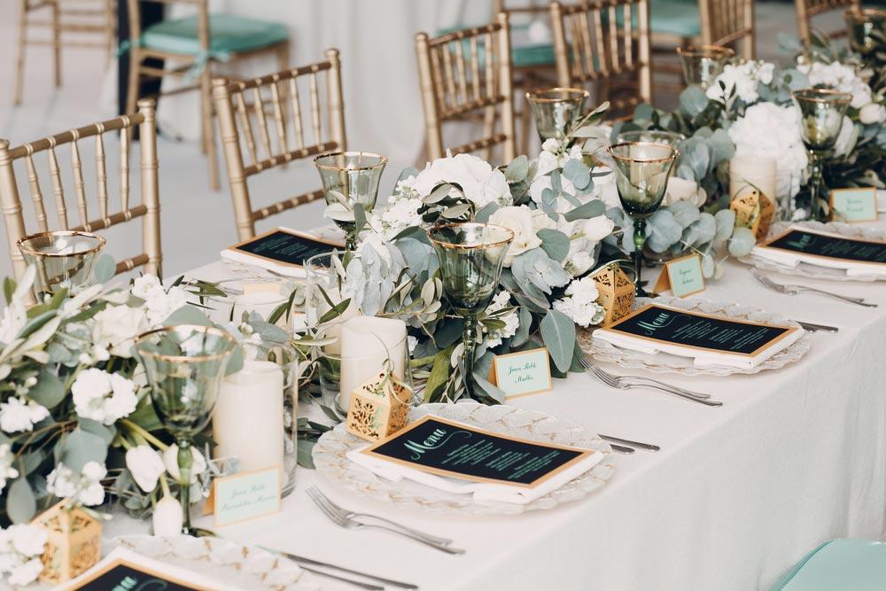 Začínající svatební hostina s bohatě prostřeným stolem, zelenými květinami, talíři, příbory a jídelníčkem.