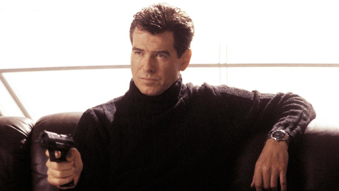 Elegantní herec Pierce Brosnan jako James Bond v černém svetru, pistolí a luxusními hodinkami.