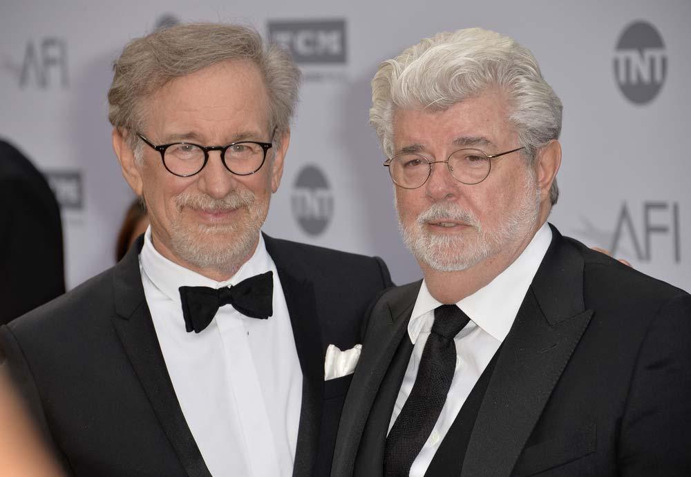 Dobře naladěný Steven Spielberg a George Lucas se nechávají fotit na filmovém večírku v elegantních černých oblecích.