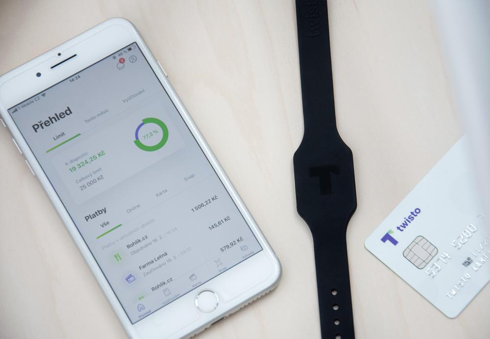 Twisto náramek ležící na stole vedle MasterCard karty a mobilu, na kterém běží Twisto aplikace.