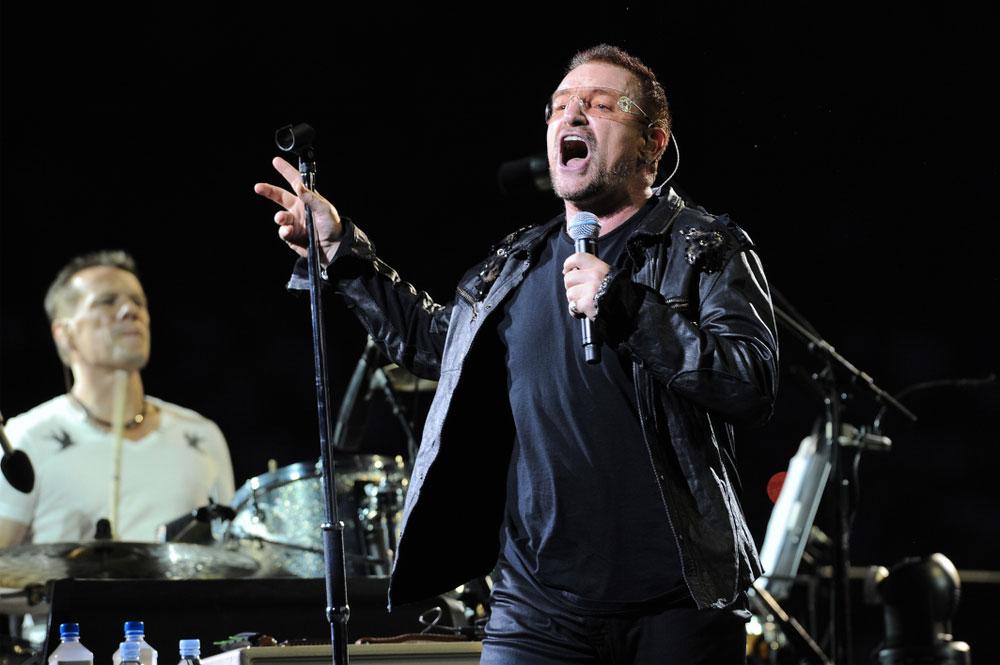 Energický Bono z kapely U2 zpívá na koncertě v černé kožené bundě.