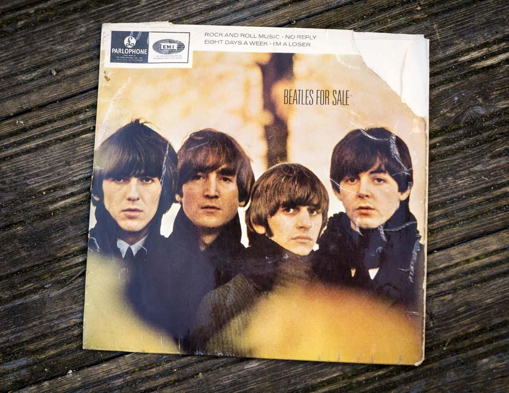 Plakát ležící na černém stole, na kterém jsou vyobrazeni všichni členové slavné kapely Beatles.