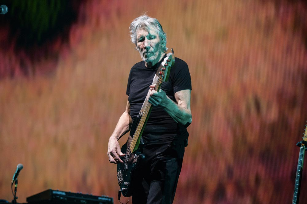 Člen kapely Pink Floyd Roger Waters koncertující s kytarou.