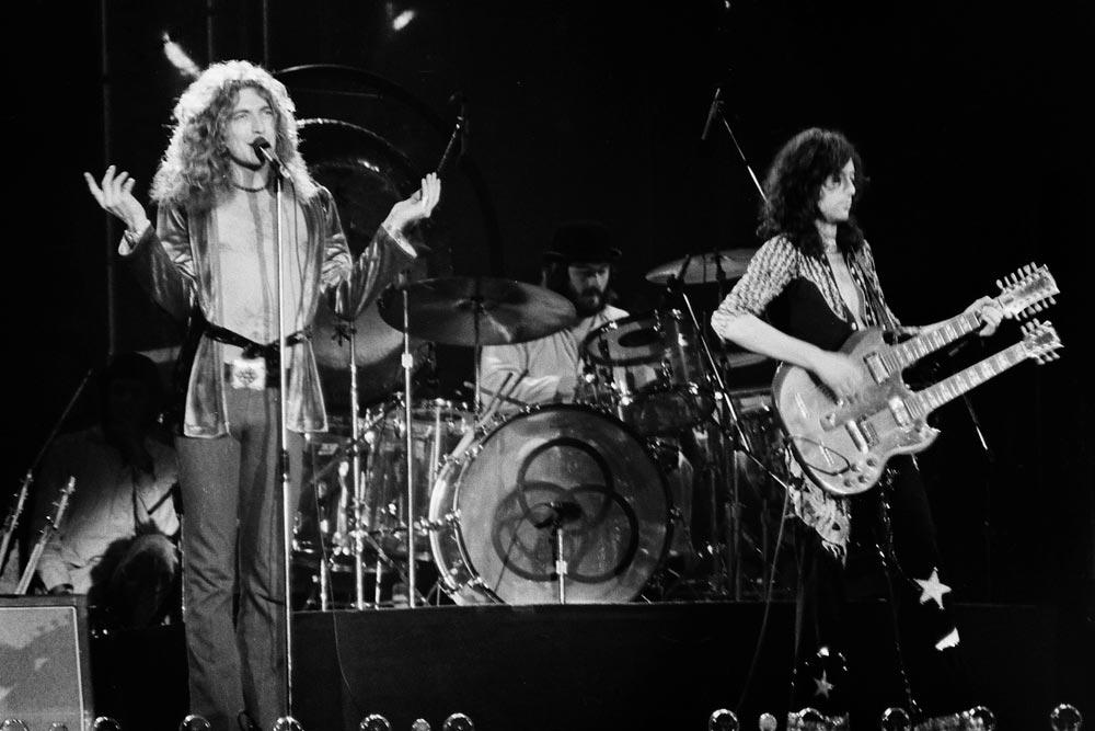 Černobílý archivní snímek zachycující koncert skupiny Led Zeppelin.