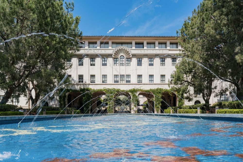 Krásná budova kalifornského Caltechu s vodní fontánou.