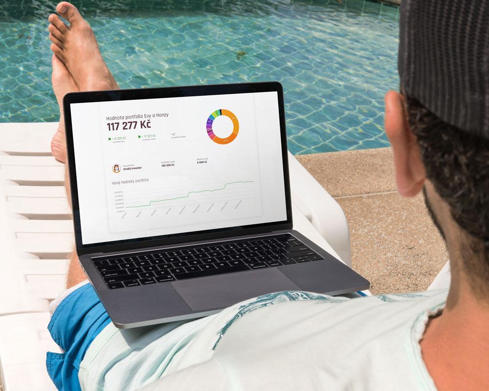 Muž u bazénu s notebookem, na kterém má otevřené portfolio investiční služby Fondee. Portfolio má hodnotu 117 277 Kč.