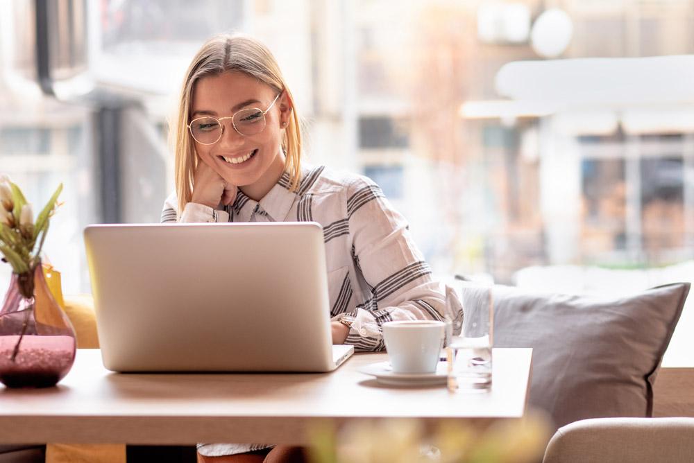 Sympatická blonďatá žena s brýlemi pracuje na notebooku v klidné kavárně.