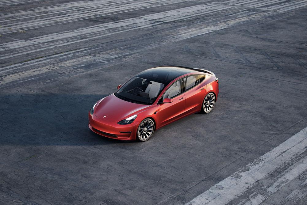 Tesla Model 3 zachycený na rozlehlém parkovišti, kde kromě tohoto auta nejsou jiné vozy.