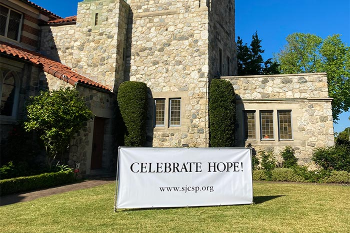 "Exterior of church with ""Celebrate Hope!"" banner."