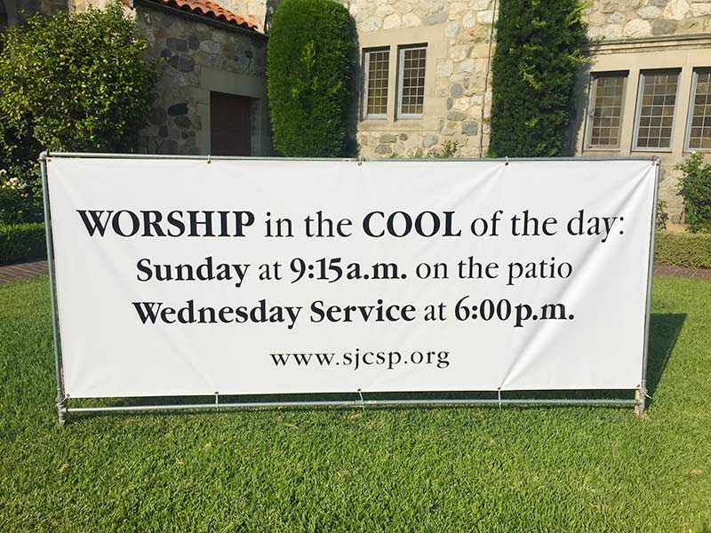"""Outdoor sign with text: """"Worship in the COOL of the day: Sunday at 9:15 am on the patio"""""""