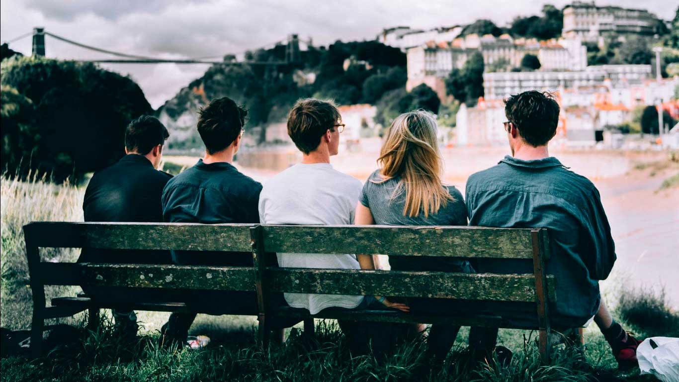 Entenda as Principais Mudanças nas Relações Afetivas do Futuro - Amigos sentados em banco vendo a cidade