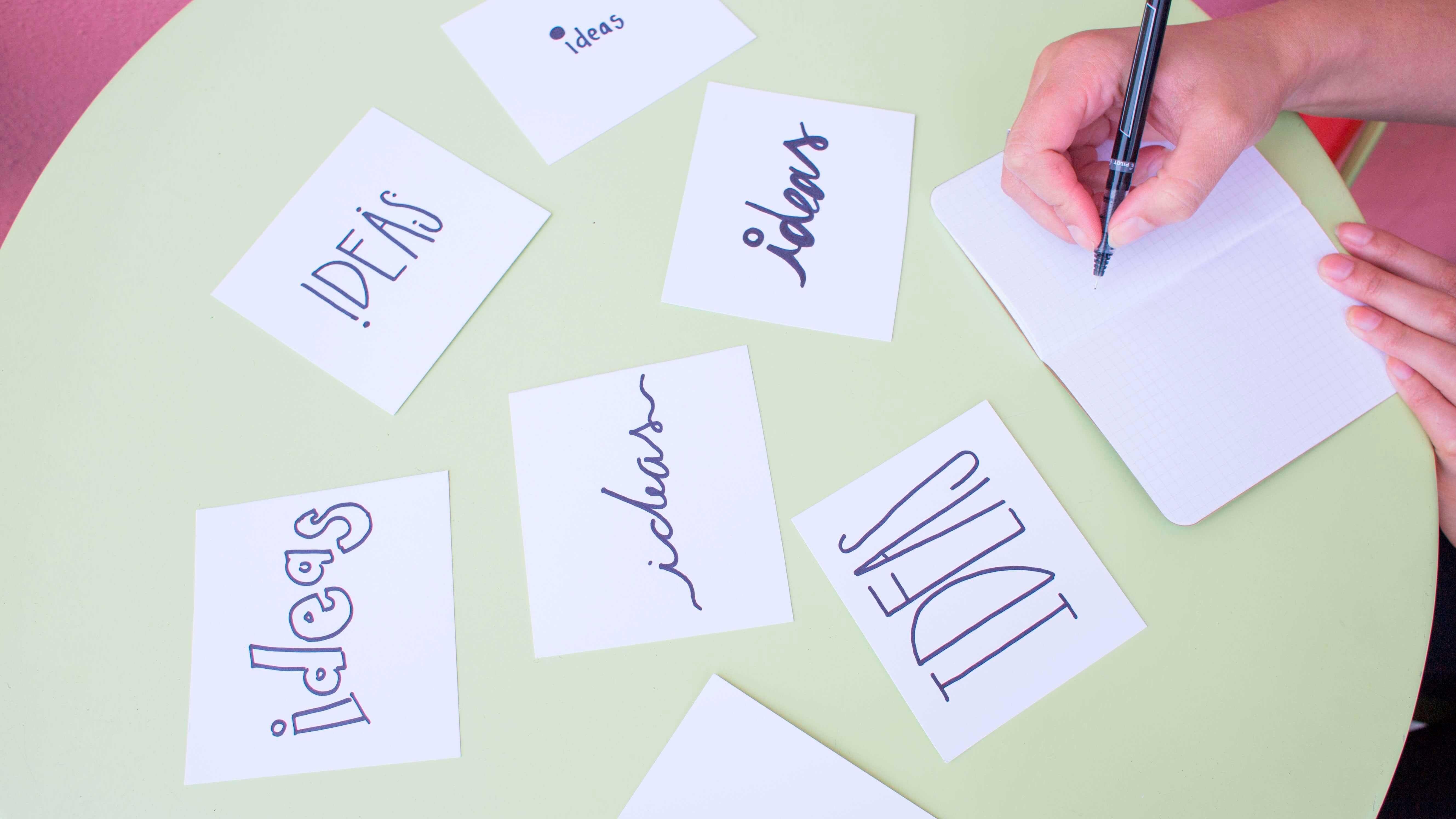 """Entenda a diferença entre criatividade e inovação - Folhas de papel com a palavra """"ideias"""" escrita"""