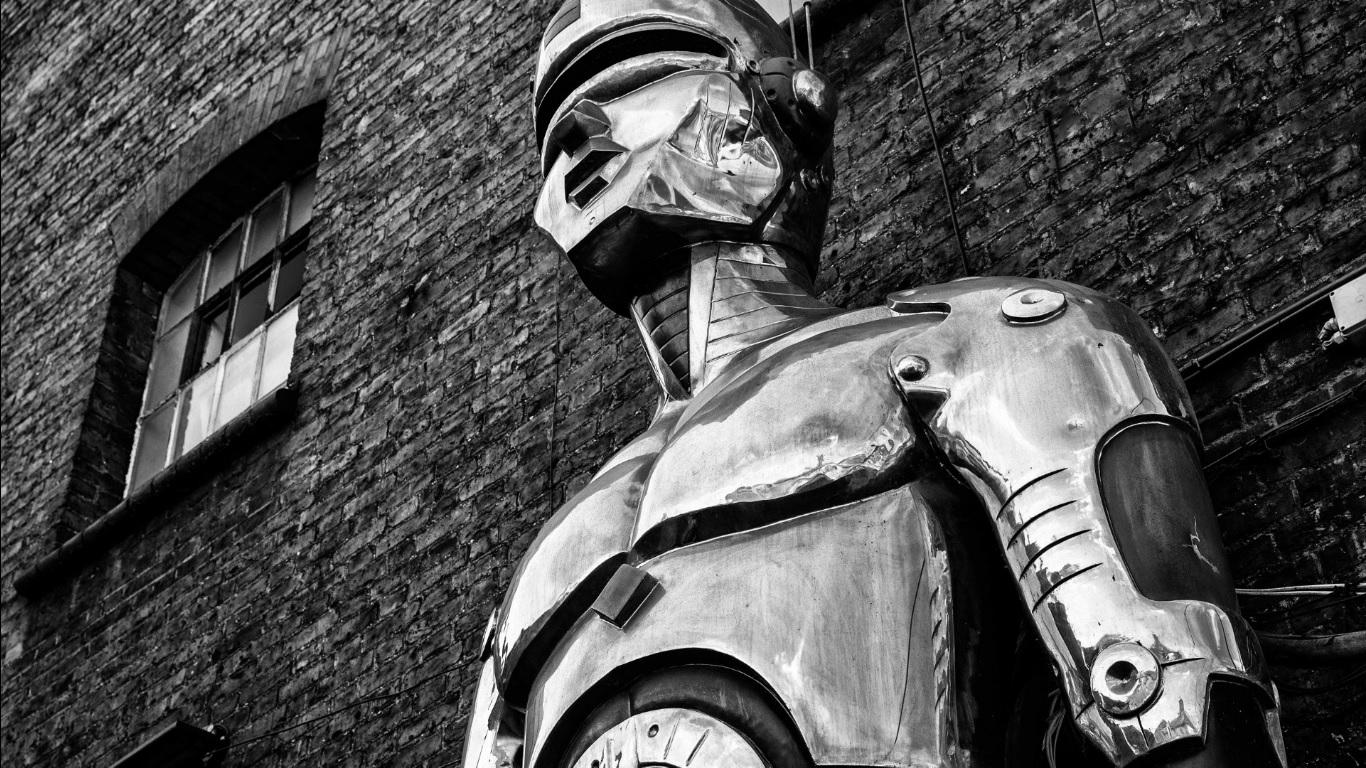 Como se preparar para a Era Pós-Digital? - Robô encostado em parede de tijolos, imagem em preto e branco.