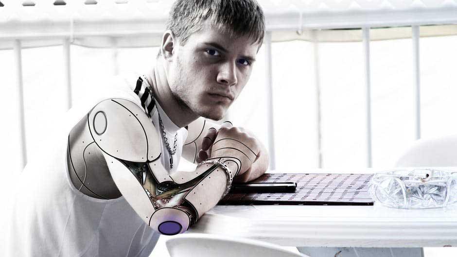 Garoto com braço robótico sentado em ambiente com fundo branco.