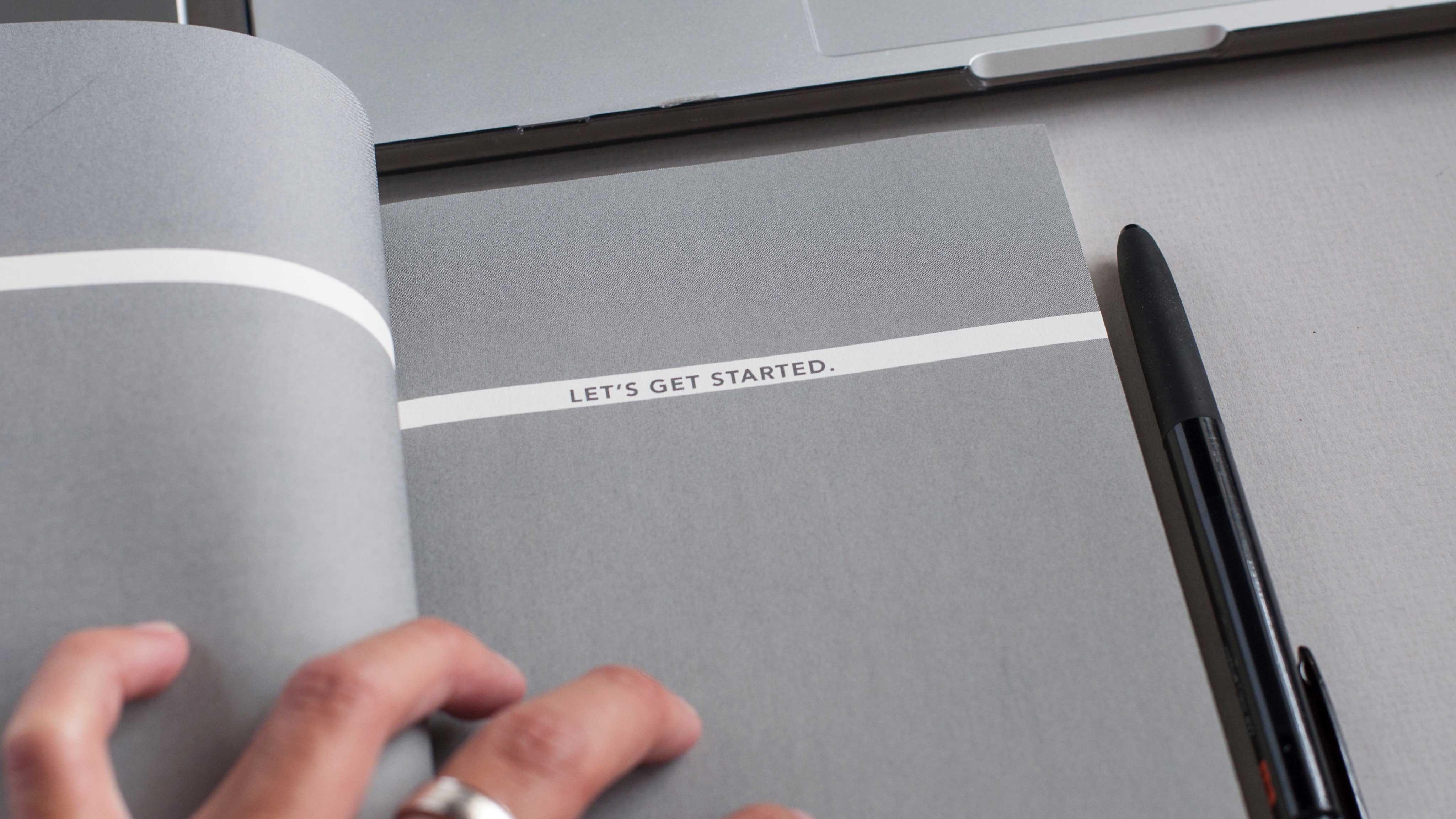 """Cadernete cinza aberta, na página pode-se ler a frase """"Let's get started""""."""