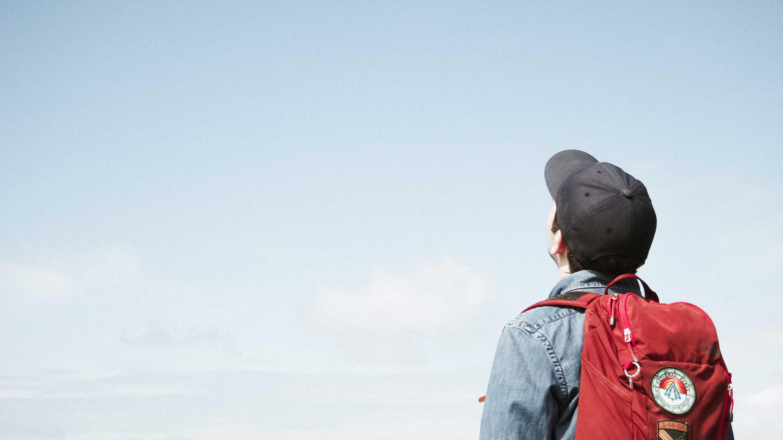 Homem de boné olhando para o céu azul
