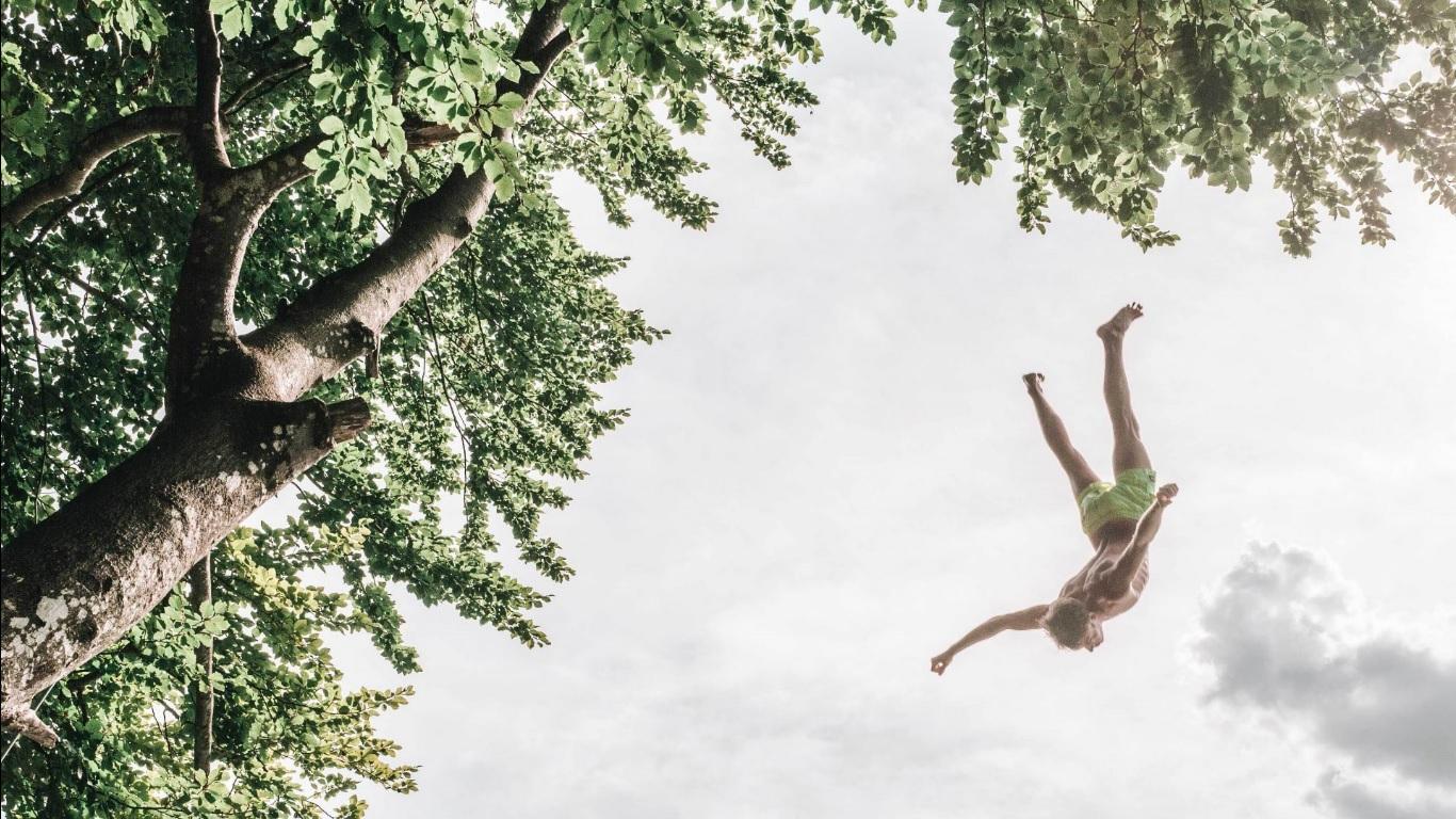 5 dicas para ser mais confiante e realizar seus sonhos - Pessoa saltando para o vazio com céu de fundo e árvores.