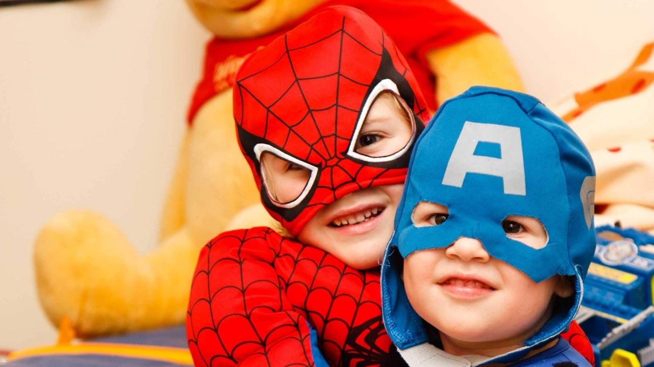 O que meu filho pode aprender com super-heróis? - Duas crianças fantasiadas de Homem Aranha e Capitão América se abraçando.