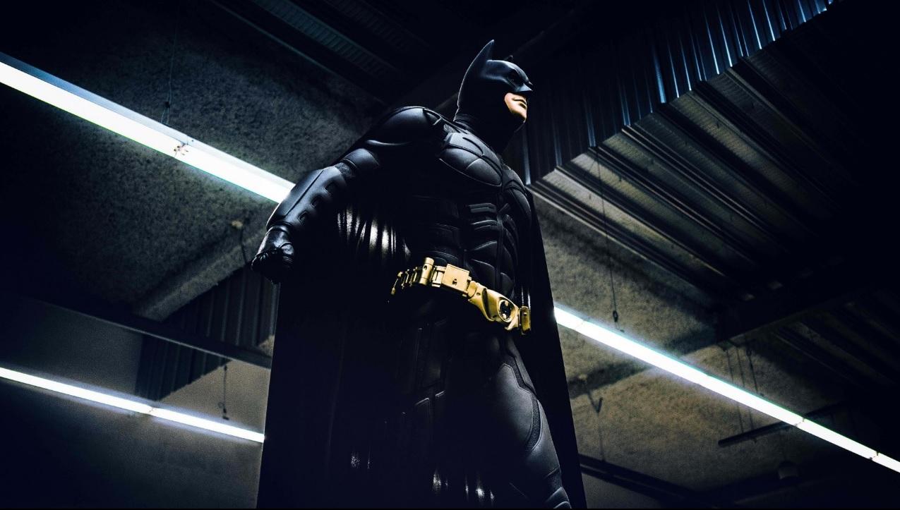Estátua do Batman em pé em um ambiente escuro