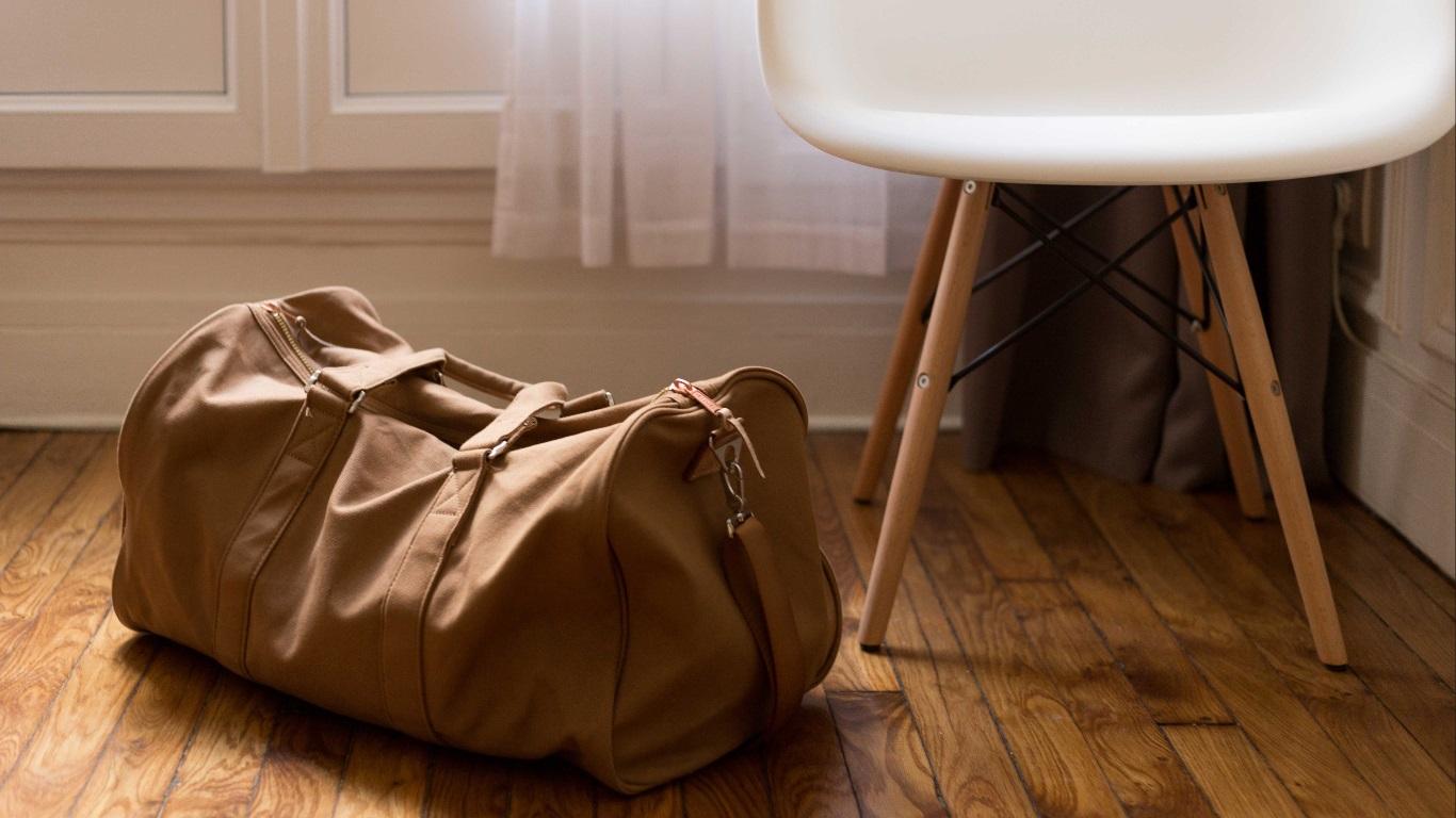 Excesso de bagagem: Autossabotagem e Crenças Limitantes. E aí, vai levar? - Sala com piso de madeira, uma mala bege está no chão ao lado de uma cadeira branca.