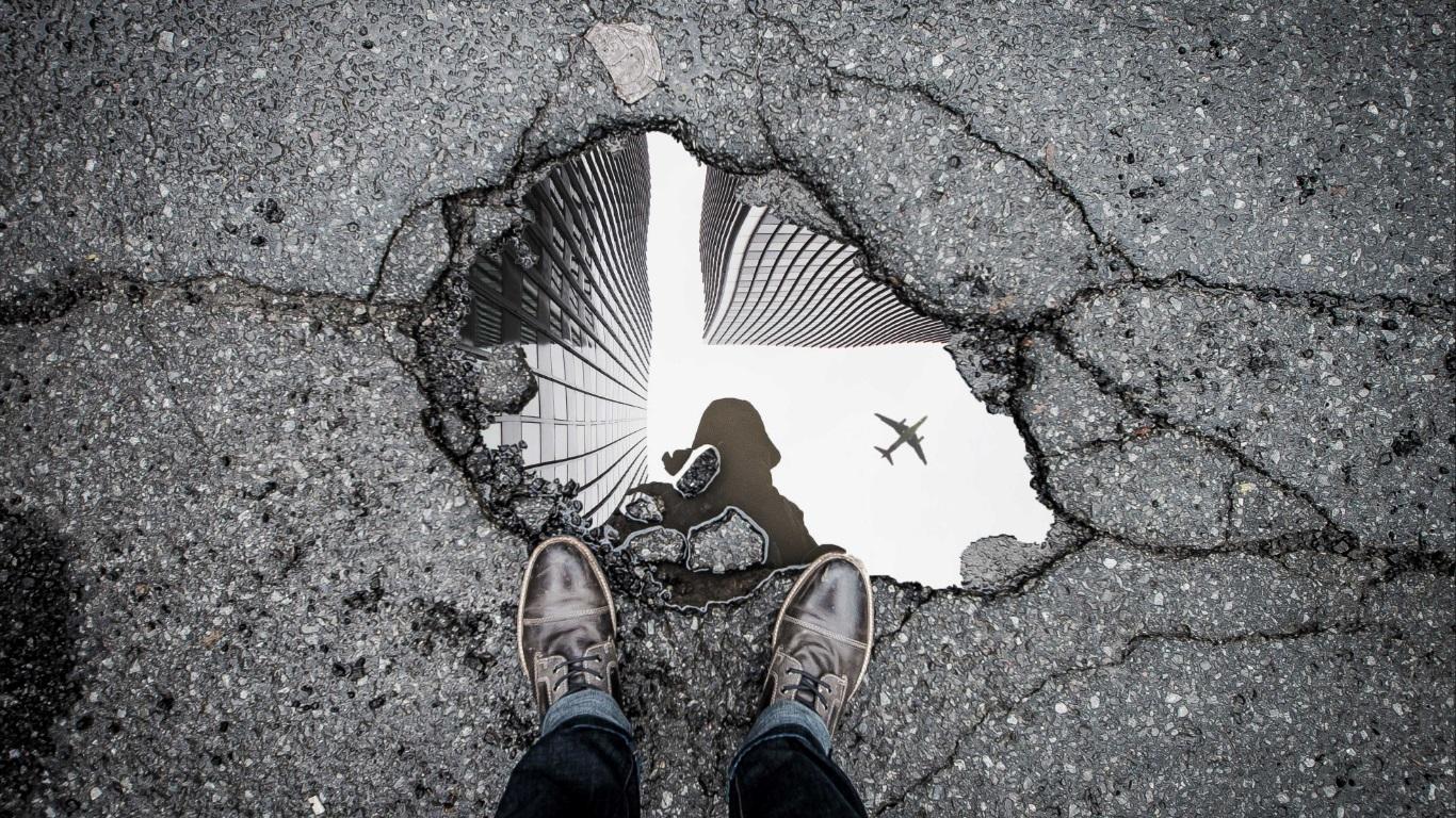 Buraco no asfalto da rua com uma poça de água na qual se vê o reflexo do fotografo.
