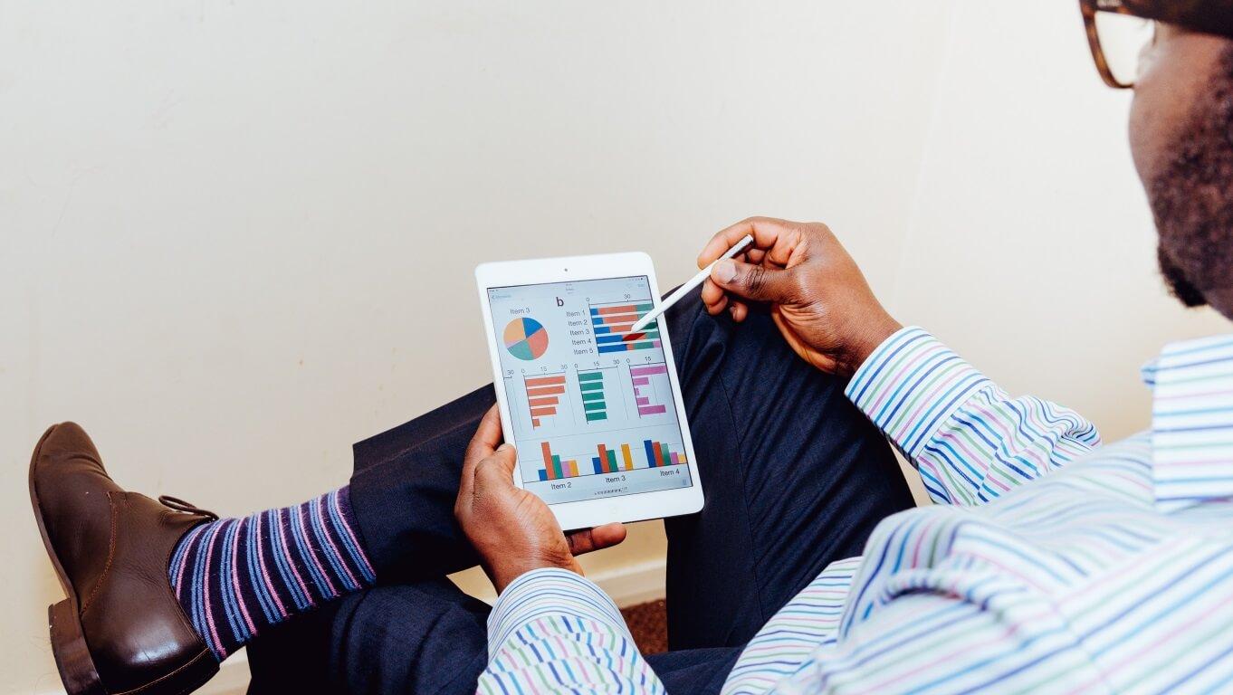 4 Dicas Valiosas para Aumentar sua Criatividade no Trabalho - Homem segurando tablet com gráficos abertos como se estivesse analisando.