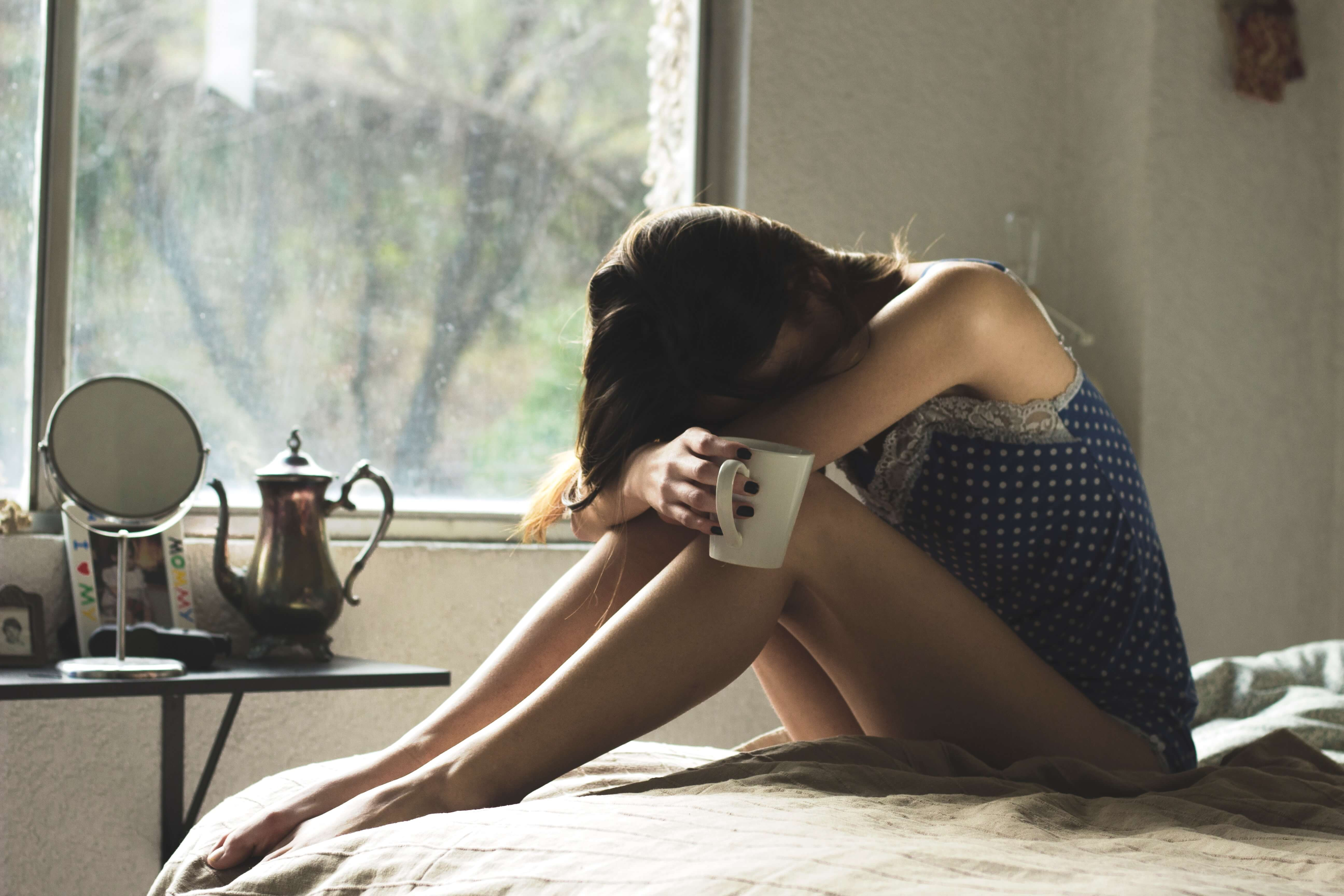 Mulher sentada na cama com a cabeça entre os joelhos como se estivesse se escondendo