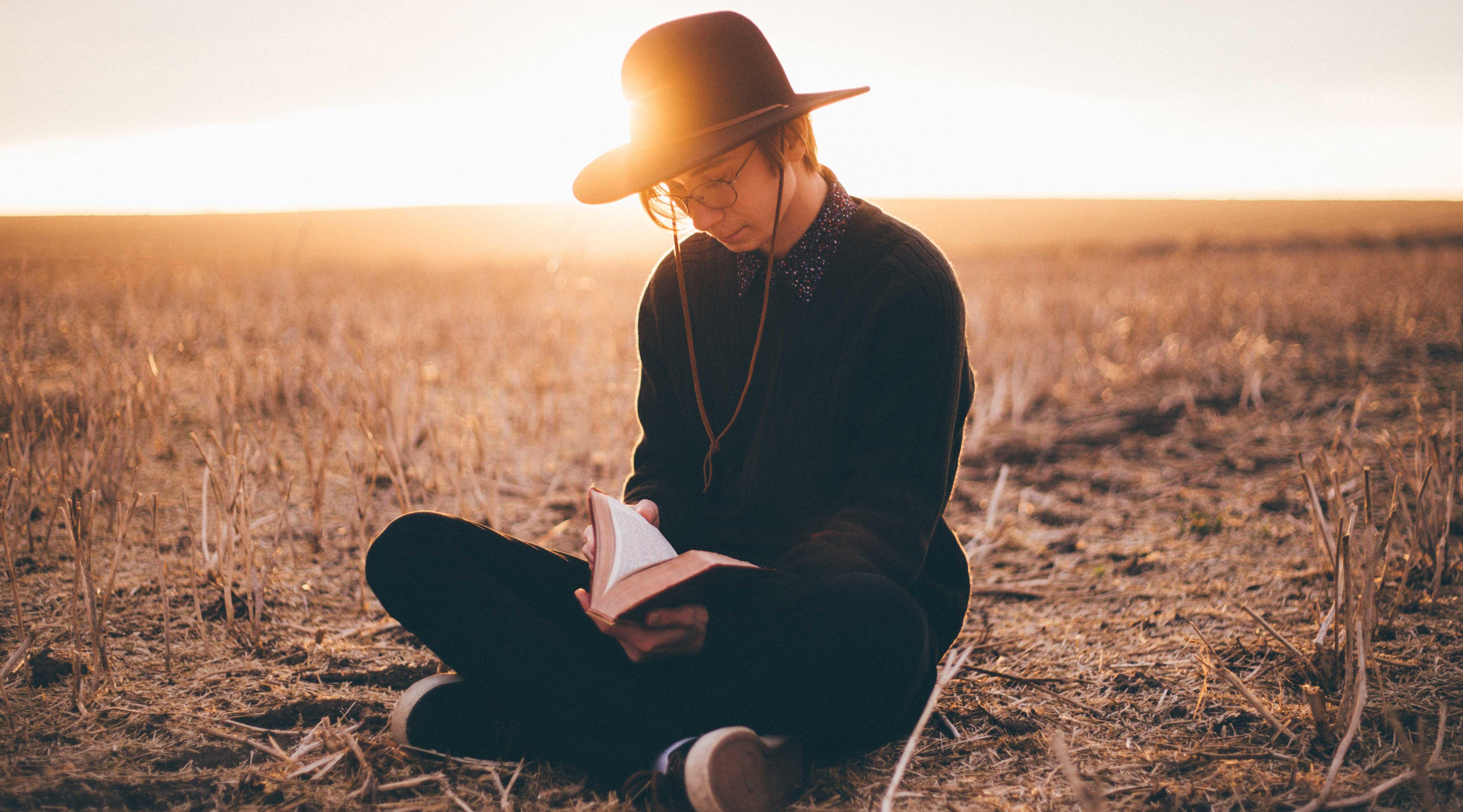 Homem sentado no chão de um campo com um livro aberto em seu colo